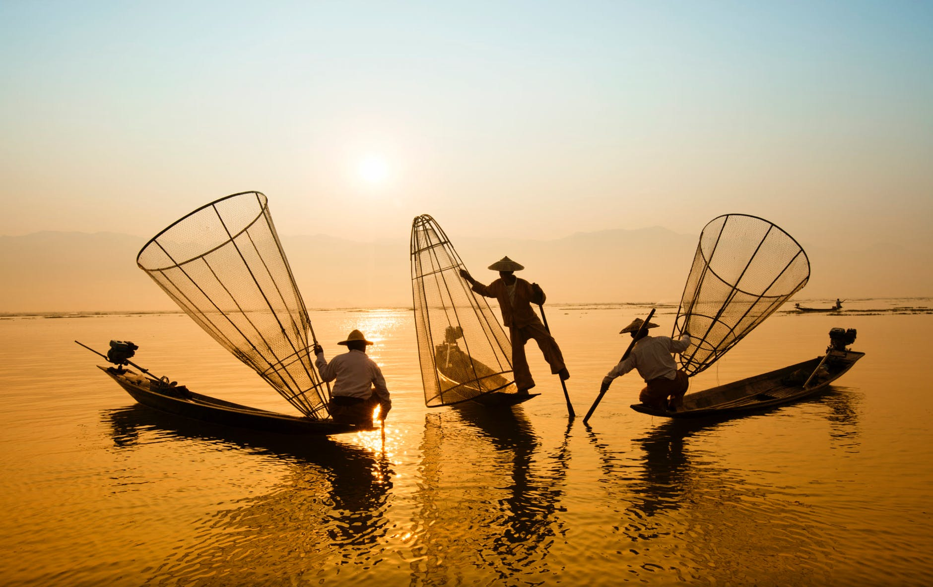 three men riding boats on body of water
